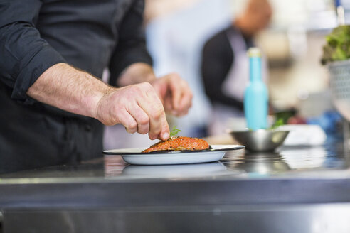 Midsection of chef garnishing food while coworker working in background at restaurant - CAVF34700