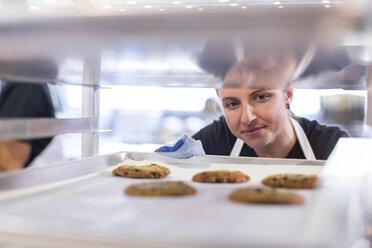 Female chef making cookies at restaurant kitchen - CAVF34703