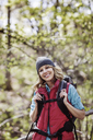 Portrait of happy female hiker standing in forest - CAVF34856