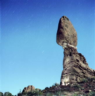 Low angle view of rock formations at Arches National Park against star trails - CAVF35018