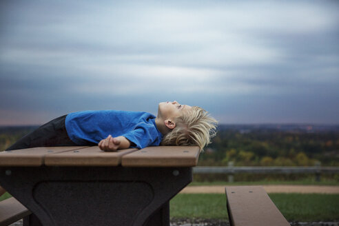 Blonde boy lying on table under overcast sky - CAVF35078