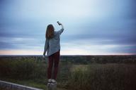 Rear view of teenage girl taking selfie at dusk - CAVF35081