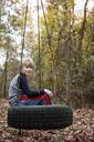 Portrait of boy sitting on tire swing - CAVF35090