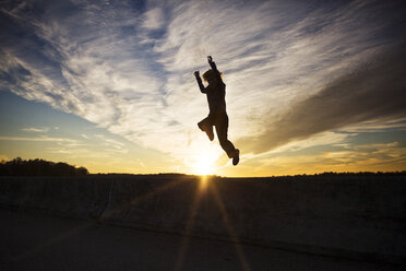 Silhouette of boy jumping against sky at sunset - CAVF35093