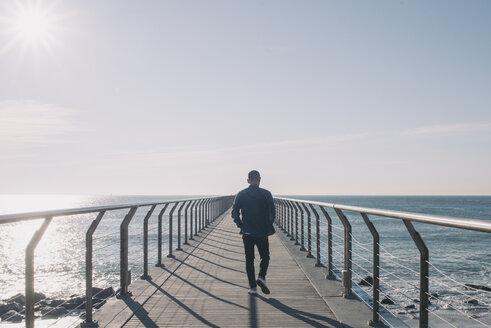 Back view of man walking on boardwalk at backlight - SKCF00398