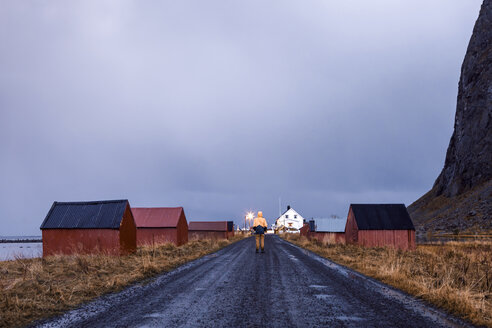 Norway, Lofoten Islands, Eggum, back view of man standing on street - WVF00976