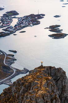 Norway, Lofoten Islands, Henningsvaer, man standing on viewing point with raising arms - WVF00994