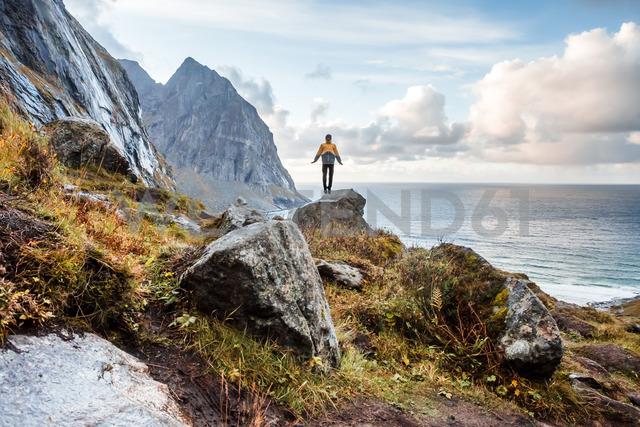 Norway, Lofoten Islands, hiker standing on rock - WVF01018