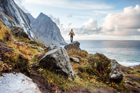 Norway, Lofoten Islands, hiker standing on rock - WVF01018