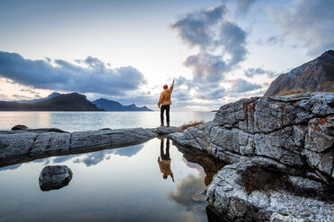 Norway, Lofoten Islands, Haukland Beach, hiker with raised arm - WVF01037
