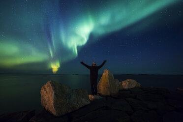 Norway, Lofoten Islands, Eggum, back view of man standing on rock admiring Northern lights - WVF01082