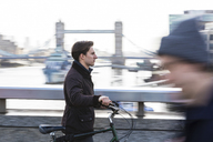 UK, London, businessman pushing  bicycle in the city - WPEF00161