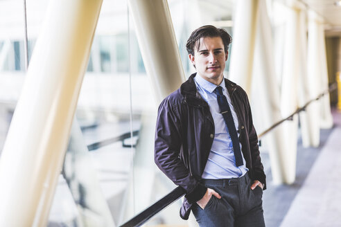 Portrait of businessman standing in skywalk - WPEF00170