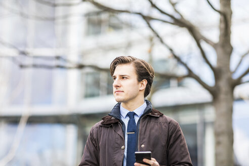 Portrait of businessman with smartphone - WPEF00173
