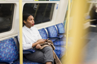UK, London, businesswoman with cell phone sitting in underground train - MAUF01366