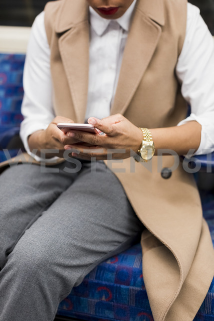 Hand of businesswoman holding cell phone in underground train - MAUF01369