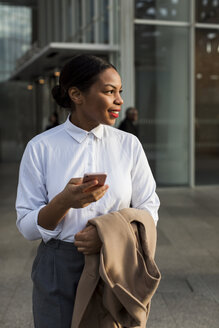 Portrait of smiling businesswoman with cell phone - MAUF01372