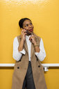 Portrait of smiling businesswoman on the phone standing in front of yellow tiled wall - MAUF01378
