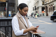 UK, London, businesswoman using cell phone - MAUF01381