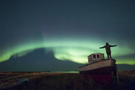 Norway, Lofoten Islands, Eggum, man admiring northern lights, standing on fishing boat - WVF01099