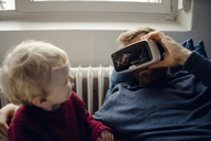 Father and son playing with VR glasses at home - KNSF03698