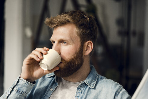 Man relaxing at home, drinking coffee - KNSF03737