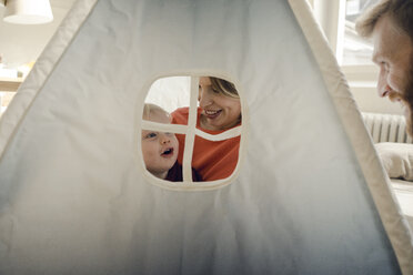 Happy family playing in a tent at home - KNSF03749