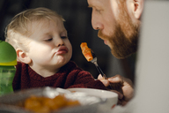 Father feeding his little son with tasty pasta - KNSF03752