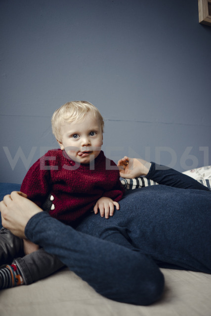 Father and son resting on couch, baby sitting on father's face - KNSF03758 - Kniel Synnatzschke/Westend61
