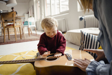 Baby boy exploring a guitar with his mother - KNSF03776