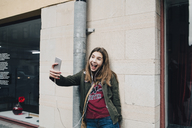Happy girl with open mouth taking selfie through smart phone while standing against wall - MASF00370