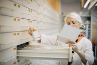 Mature female pharmacist holding prescription paper checking medicine by drawer in store - MASF00388
