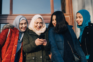 Happy female Muslim friends sharing smart phone standing against entrance door in city - MASF00418