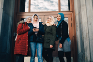Low angle portrait of smiling multi-ethnic Muslim friends standing against door - MASF00424
