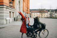 Portrait of happy young woman showing peace sign sitting behind friend on bicycle in city - MASF00427