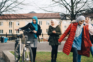 Happy multi-ethnic female friends walking with bicycle on grass in city - MASF00430