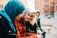 Female friends wearing hijabs sitting in city sharing digital tablet - MASF00433
