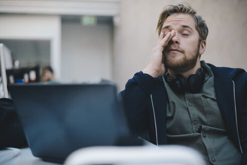 Tired computer programmer rubbing eyes while sitting in office - MASF00484
