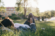 Teenage girl using smart phone while lying on grass - MASF00502