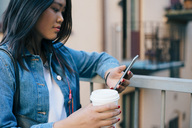 Teenage girl using smart phone while holding disposable coffee cup by railing - MASF00505