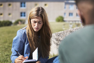 Woman writing on book while sitting with friend at university campus - MASF00562