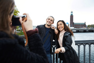 Woman photographing smiling friends standing on bridge by railing in city against clear sky - MASF00586