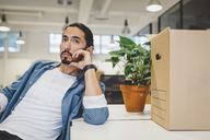 Thoughtful young businessman sitting by cardboard box and potted plant in new office - MASF00592