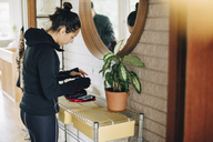 Woman checking diabetes kit while standing in front of mirror at home - MASF00601