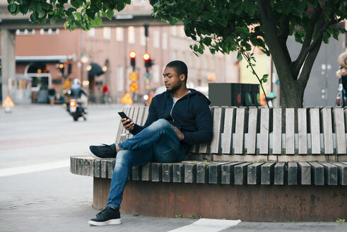 Young man using smart phone while sitting with legs crossed on bench in city - MASF00625