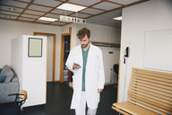 Young doctor using smart phone while walking in corridor at hospital - MASF00634