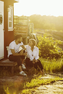 Young couple talking while sitting at log cabin on sunny day - MASF00673