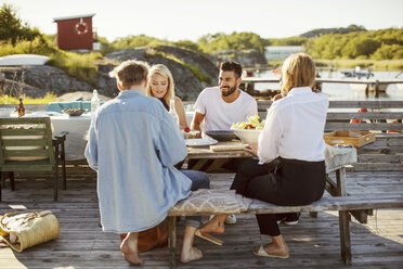 Young multi-ethnic friends enjoying summer lunch at harbor - MASF00679