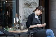 Young female owner using smart phone while sitting by table against store - MASF00688