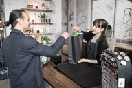 Young female owner giving shopping bag to male customer at store - MASF00694